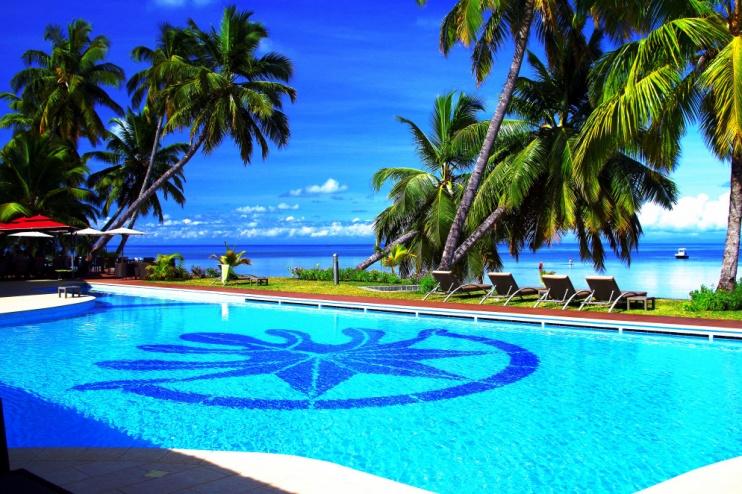 Außenpool unter Palmen direkt am Strand